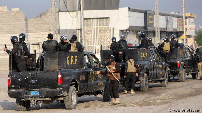Iraqi security forces are seen on military vehicles during ongoing anti-government protests in Basra