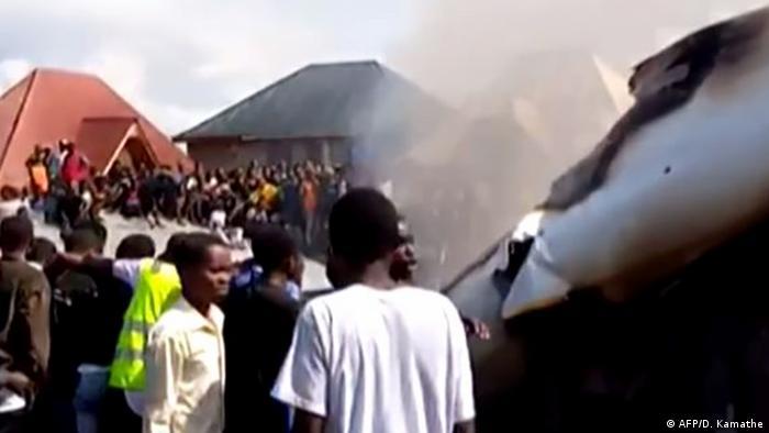 People gather around the smoking wreckage of the plane