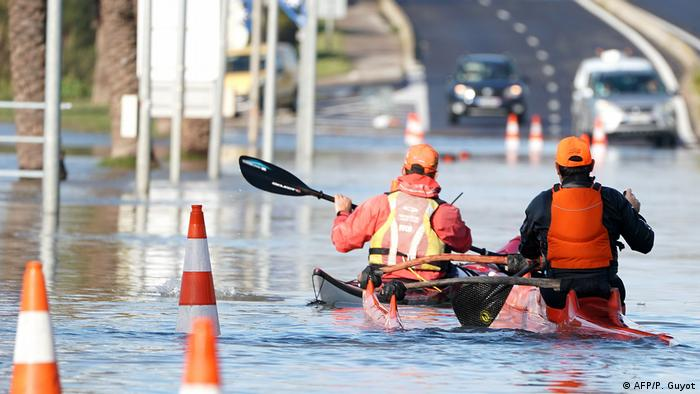 Two person paddle their kayak through flooded road in Palavas-les-Flots
