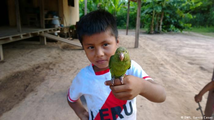Un niño sostiene un ave en la comunidad indígena de Santa Clara de Uchunya, en Perú.