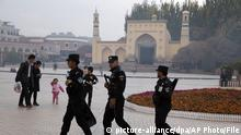 FILE - In this Nov. 4, 2017 file photo, Uighur security personnel patrol near the Id Kah Mosque in Kashgar in western China's Xinjiang region. Classified documents, leaked to a consortium of news organizations, lay out the Chinese government's deliberate strategy to lock up ethnic minorities to rewire their thoughts and even the language they speak. (AP Photo/File) |