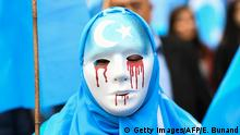 TOPSHOT - A person wearing a white mask with tears of blood takes part in a protest march of ethnic Uighurs asking for the European Union to call upon China to respect human rights in the Chinese Xinjiang region and ask for the closure of re-education center where Uighurs are detained, during a demonstration around the EU institutions in Brussels on April 27, 2018. (Photo by Emmanuel DUNAND / AFP) (Photo by EMMANUEL DUNAND/AFP via Getty Images)
