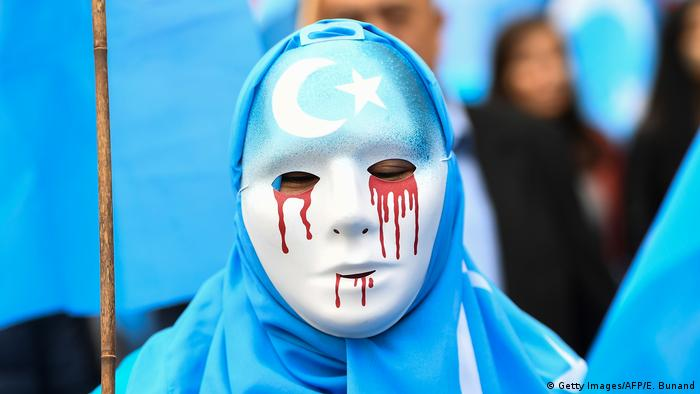 A person wearing a white mask with tears of blood takes part in a protest march of ethnic Uyghurs asking for the European Union to call upon China to respect human rights in the Chinese Xinjiang region