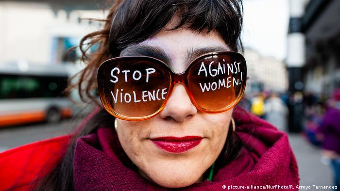 A woman wearing glasses with stop violence against women written on them