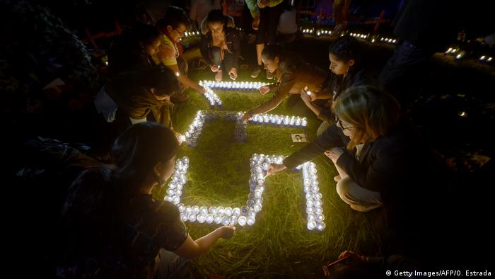 Women kneeling in front of lit candles spelling out 571 Guatemala(Getty Images/AFP/O. Estrada)