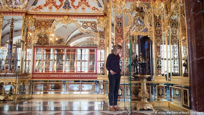 A woman stands in front of a display case in the Jewel Room of the historic Green Vault, which is decorated opulently