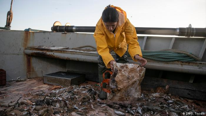A scientist aboard a fishing trawler holding up a plastic bag