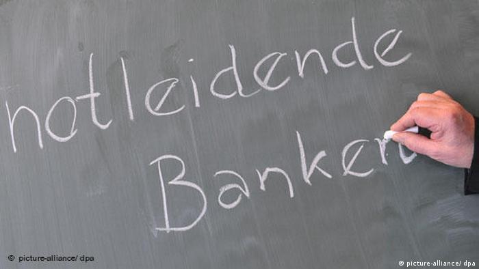 Jemand schreibt mit Kreide notleidende Banken auf eine Tafel (picture-alliance/ dpa)