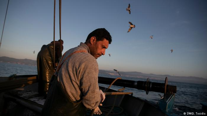 A fisherman checking a line on a boat