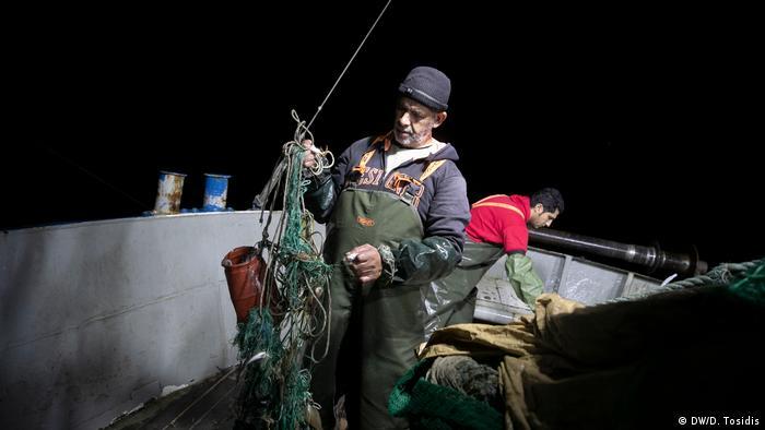 A fisherman untangling a net