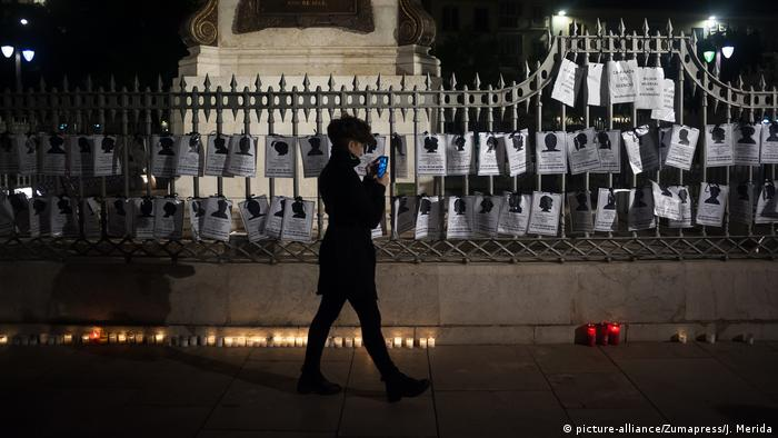 Woman walking past placards hung up on gate at night (picture-alliance/Zumapress/J. Merida)
