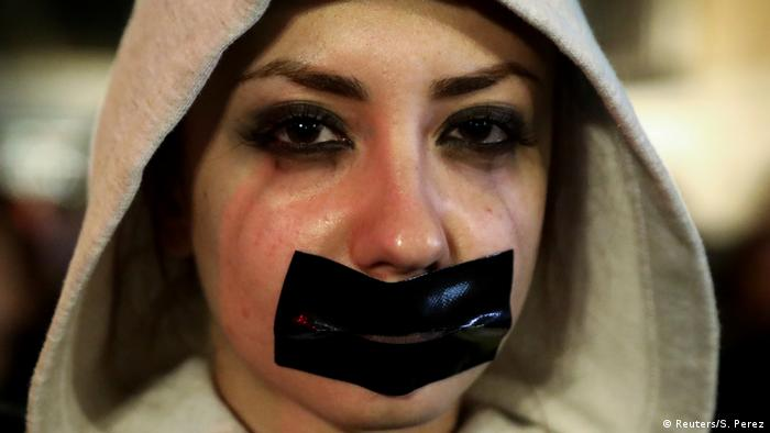 Woman with hood and tape across her mouth (Reuters/S. Perez)