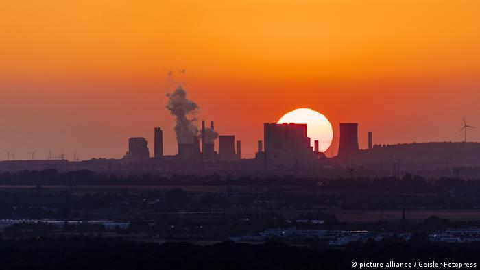 Usinas termoelétricas vistas no horizonte, diante do pôr do sol