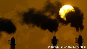 Дымящие трубы на фоне солнца