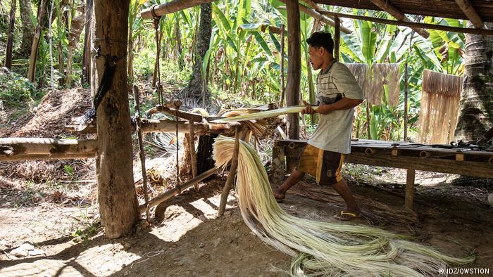 Un hombre trabaja con las fibras de plátano.