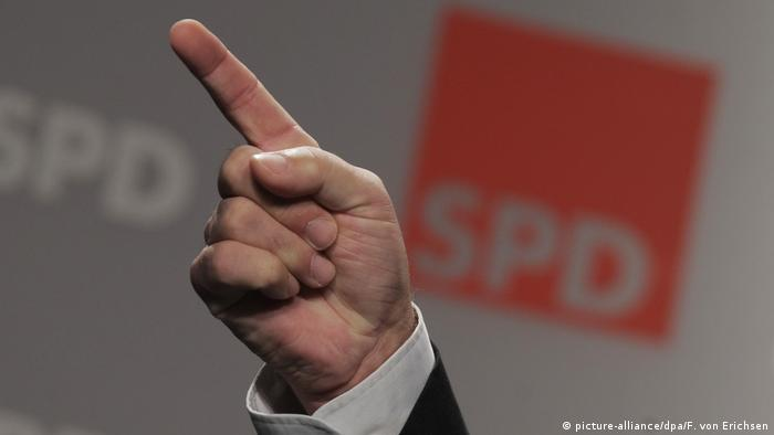 A man's hand raised with the SPD logo in the background