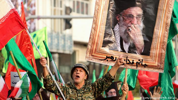 A government supporter chants slogans with ayatollah's picture in the background (Getty Images/AFP/A. Kenare)