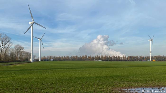 Smoke from a coal-burning power plant rises behind the wind farm in Langerwehe, Germany