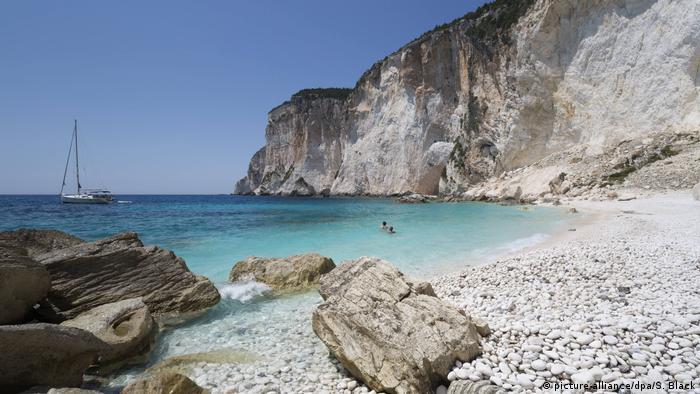 Erimitis beach with cliffs on Corfu island, Greece. Yacht moored offshore