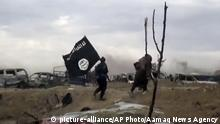 This frame grab from video posted online Monday, March 18, 2019, by the Aamaq News Agency, a media arm of the Islamic State group, shows IS fighters walking as they hold the group's flag inside Baghouz, the Islamic State group's last pocket of territory in Syria. U.S.-backed Syrian forces fighting the Islamic State group announced Tuesday they have taken control over an encampment in an eastern Syrian village where IS militants have been besieged for months, refusing to surrender. (Aamaq News Agency via AP) |