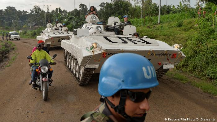 Congolese men ride on a motorcycle past peacekeepers from India