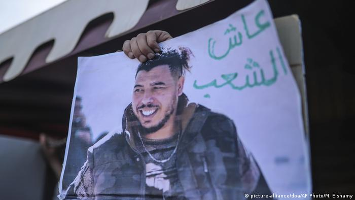 Protesters with a photo of Moroccan rapper Gnawi