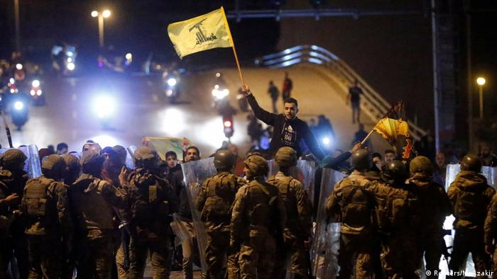 Supporters of the Lebanese Shiite groups Hezbollah and Amal carry flags (REUTERS/Mohamed Azakir)