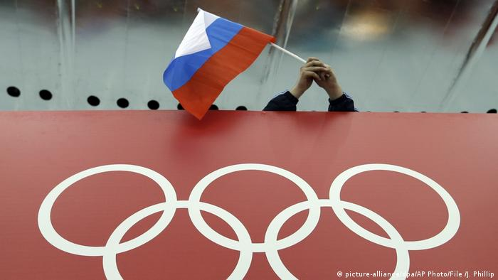 A Russian flag held near a sign featuring the Olympic Rings (AP Photo/David J. Phillip, File)