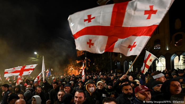 Protesters demanding the government's resignation and early parliamentary polls march towards the parliament in Tbilisi