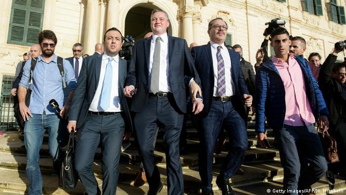 Konrad Mizzi walks down the steps of a government building