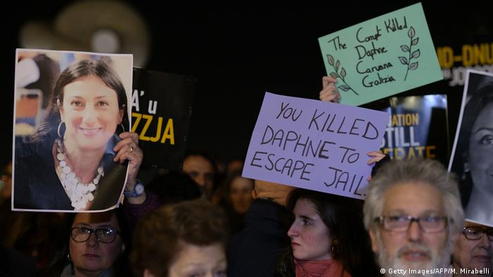 Protesters hold up signs with Daphne Caruana Galizia's face on them at a demonstration
