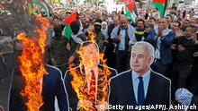 TOPSHOT - Palestinian protesters burn cardboard cutouts of US President Donald Trump, his State Secretary Mike Pompeo, and Israeli Prime Minister Benjamin Natanyahu, during a demonstration in the center of Nablus city in the occupied West Bank on November 26, 2019, against the US policy shift on Israeli settlements in Palestinian Territories. - Pompeo announced last week that the United States no longer considers Israeli settlements in the West Bank and Israeli-annexed east Jerusalem illegal, a shift that came nearly two years after President Donald Trump overturned decades of policy by recognising the contested holy city of Jerusalem as Israel's capital, sparking Palestinian and Arab anger. (Photo by Jaafar ASHTIYEH / AFP) (Photo by JAAFAR ASHTIYEH/AFP via Getty Images)