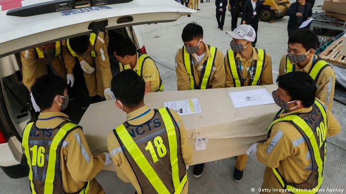 Vietnam's Noi Bai international airport staff carrying caskets