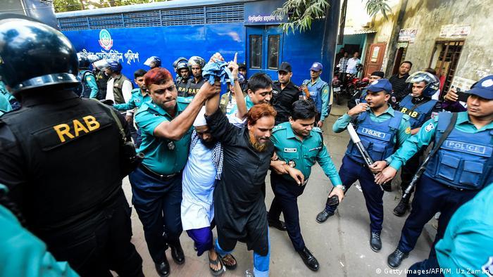 La policía escolta a dos de los acusados hasta el tribunal antes de emitirse la sentencia a muerte por el ataque, Dacca, Bangladés (27.11.2019)