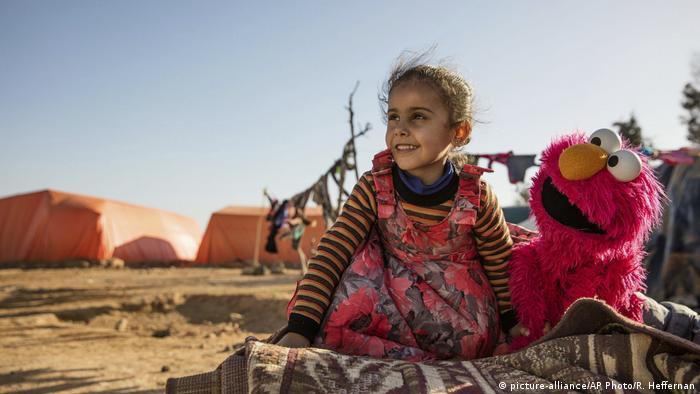 Una niña juega con el personaje de Plaza Sésamo, Elmo, en un asentamiento informal en Jordania