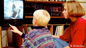 Child watches television with his mother