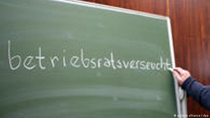 Jemand schreibt mit Kreide das Wort betriebsratsverseucht auf eine Tafel (picture alliance / dpa)