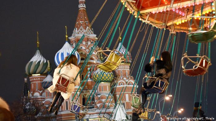 Russia | people of a chain swing ride at night in front of the Kremlin (picture-alliance/dpa/C. Thiele)