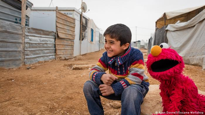 Elmo and a smiling boy in a refugee camp in Jordan
