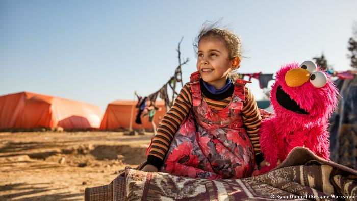 A girl and Elmo at a refugee camp