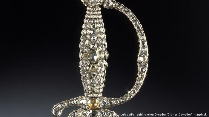 A sword with a jewel-covered hilt