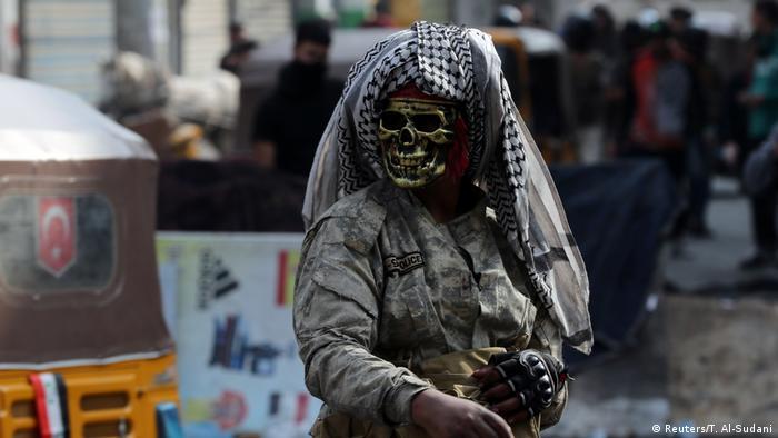 Manifestante mascarado de caveira, com turbante árabe