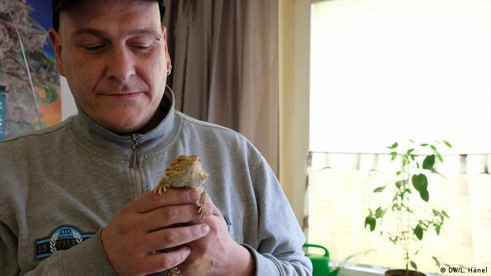 Andre Kurkowiak in his apartment in Düsseldorf, holding a lizard (DW/L. Hänel)