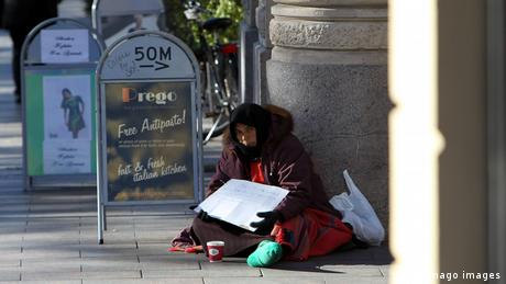 A homeless woman sits on the street holding a sign