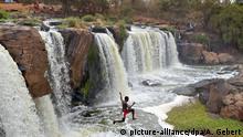 Ein Junge springt im Nationalpark Fourteen Falls, etwa 60 Kilometer vor Nairobi, der Hauptstadt von Kenia gelegen, einen Wasserfall hinunter (Foto vom Oktober 2006). Die Landschaft am Athi-Fluss weist 14 hintereinanderliegende Wasserfälle auf. Foto: Andreas Gebert +++(c) dpa - Report+++ | Verwendung weltweit