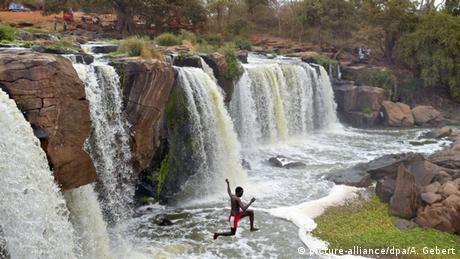 A boy leaps into a pool beneath a waterfall at Fourteen Falls, Kenya