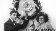 Symbolbild schwarz-weiß: Ein junges Paar steht mit Sektgläsern in der Hand da und weist auf eine Uhr, deren beide Zeiger auf der Zwölf stehen