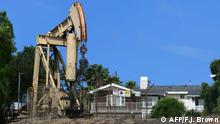 A home is seen beside a pumpjack in an oil wel1 on September 25, 2019 in Signal Hill, California, where oil has been pumped since the 1920's. - For most outsiders, Los Angeles is all about Hollywood, palm trees and sunny skies. But the huge metropolis that is home to nearly four million people is also the largest urban oil field in the country. Hundreds of active oil wells sit in densely populated and mostly low-income neighborhoods of the county, butting up against schools, homes, parks, shopping malls or cemeteries. (Photo by Frederic J. BROWN / AFP)