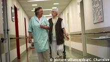 Heike Jakobi vom ehrenamtlichen Kranken-Lotsendienst begleitet am Freitag (20.07.2012) die Patientin Helga Berger (r) von der Krankengymnastik in ihr Zimmer im Albertinen-Haus in Hamburg. Als Grüne Dame leitet Jakobi ehrenamtlich den Lotsendienst im Albertinen-Haus, einer Spezialeinrichtung für Altersmedizin. Der Lotsendienst ist nur ein Bereich in dem Grüne Damen, aber auch einige Grüne Herren tätig sind. 80 Ehrenamtliche, die meisten von ihnen Rentner, arbeiten im Besuchsdienst, in der Bibliothek, betreuen Demenzkranke oder begleiten Sterbende. Foto: Christian Charisius dpa/lno (zu dpa-Korr: Grüne Dame mit Herz - Heike Jakobi hilft Kranken ehrenamtlich vom 23.07.2012) | Verwendung weltweit