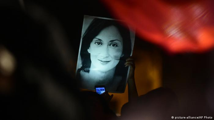 A protester holds up an image of murdered journalist Daphne Caruana Galizia
